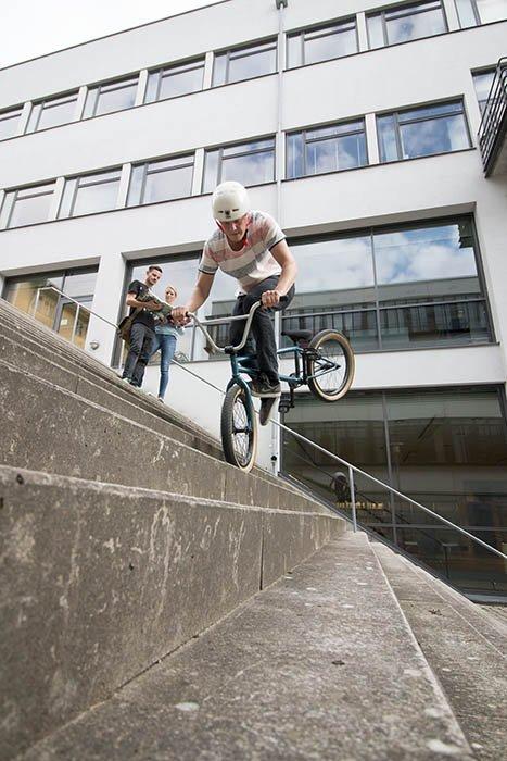 Webbprogrammerar-oscar cyklar på framhjulet i trappan, en gång till.